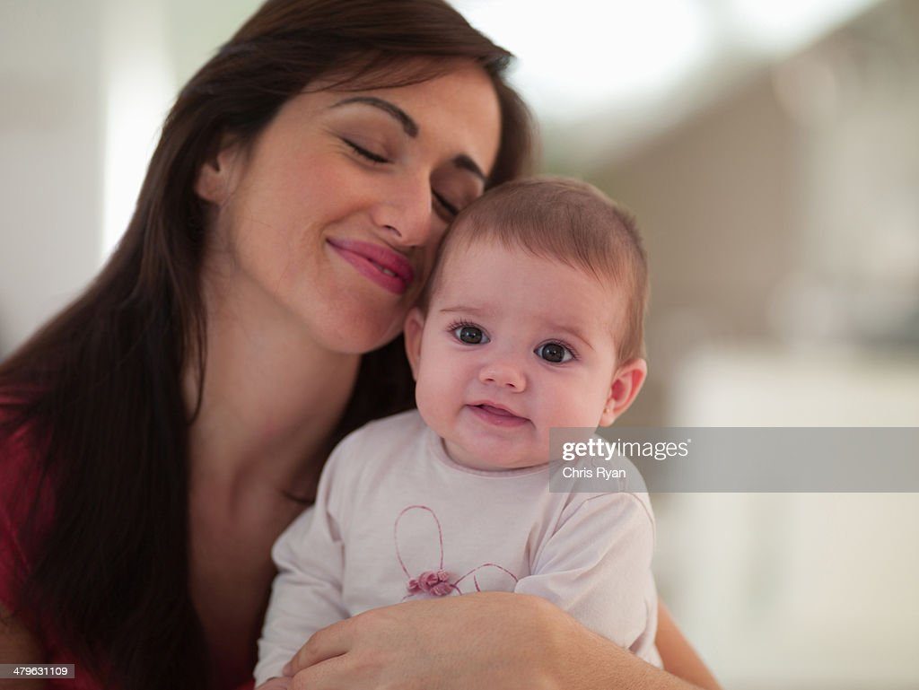 Mother posing with baby daughter : Stock Photo