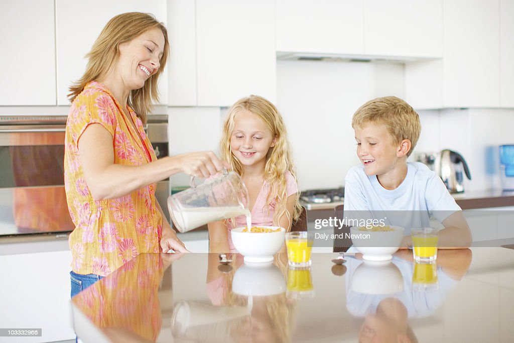 Mother pouring milk for children in kitchen : Stock Photo