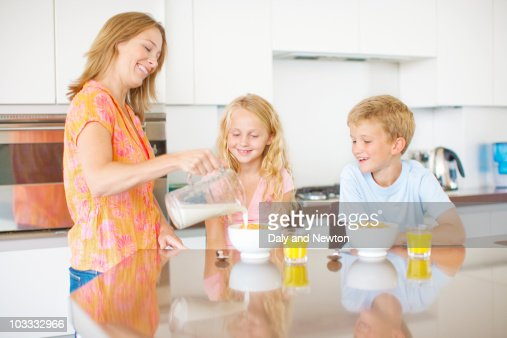 Mother pouring milk for children in kitchen : Foto de stock