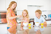 Mother pouring milk for children in kitchen