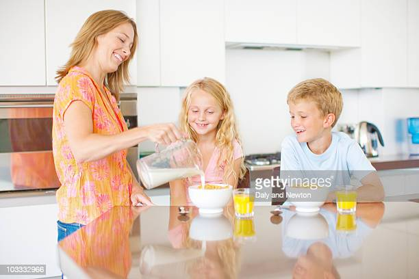 Mother pouring milk for children in kitchen
