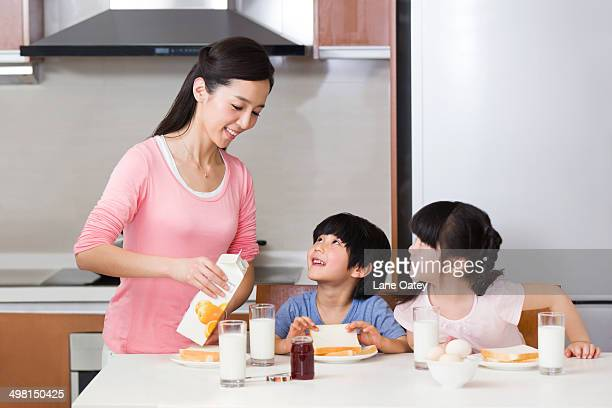Mother pouring milk for children