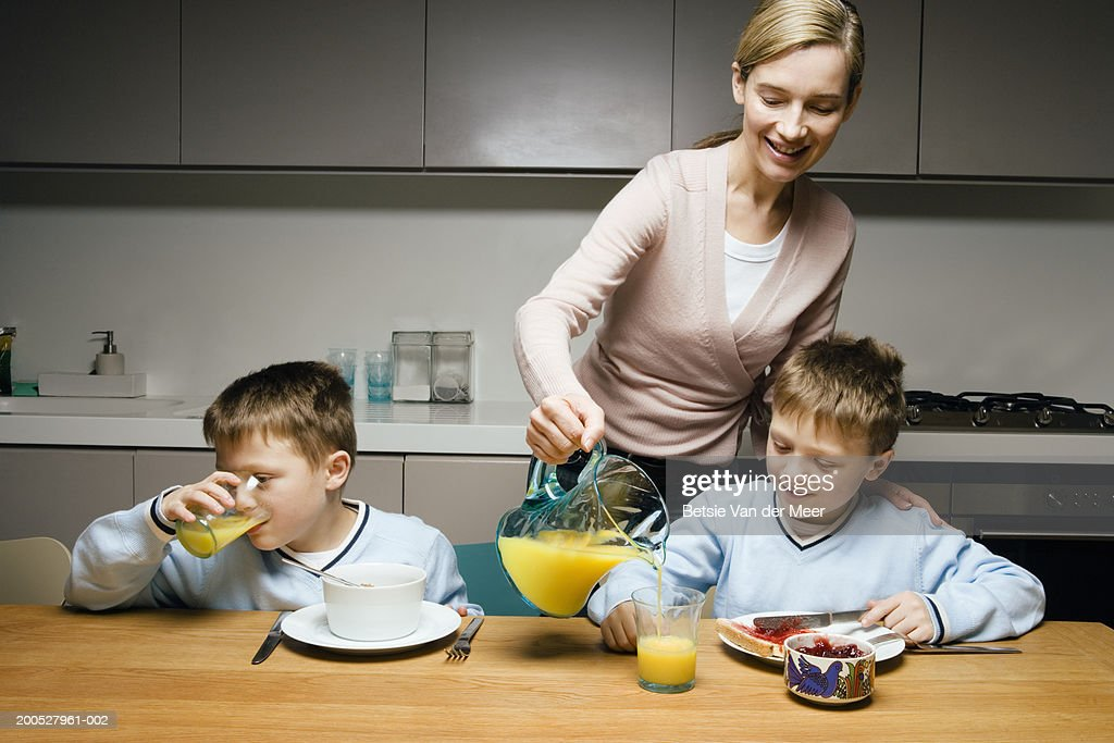 Mother pouring orange juice for twin boys (8-10) at breakfast : Stock Photo
