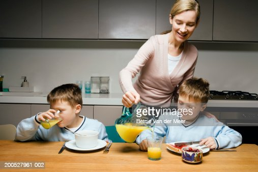 Mother pouring orange juice for twin boys (8-10) at breakfast : Stock-Foto