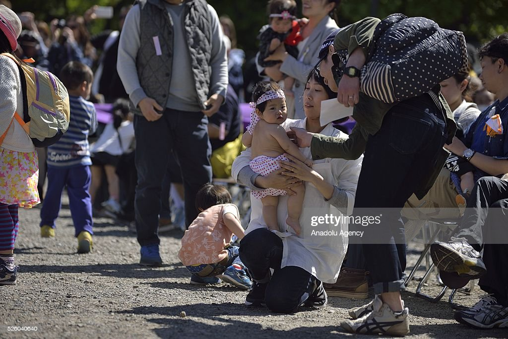 A mother prepares her baby to take part during the Nakizumo or crying baby sumo contest at Sensoji Temple on April 29, 2016 in Tokyo, Japan. Babies compete crying at this traditional festival which is believed to bring growth and good health to the infants.