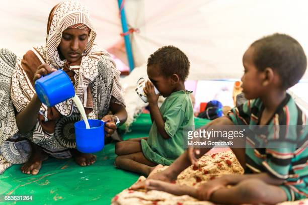 A mother prepares milk from milk powder for her children Unicef feeding in a village in the Somali region of Ethiopia where Pastorale settled because...