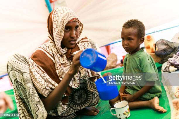 A mother prepares milk from milk powder for her son Unicef feeding in a village in the Somali region of Ethiopia where Pastorale settled because of...