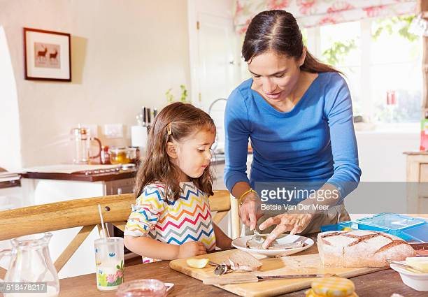 Mother prepares sandwiches, daughter looks on.