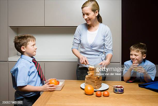 Mother preparing sandwiches for twin boys (8-10)