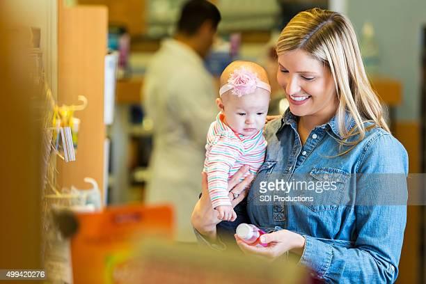 Mother purchasing cold & fever medicine for infant daughter