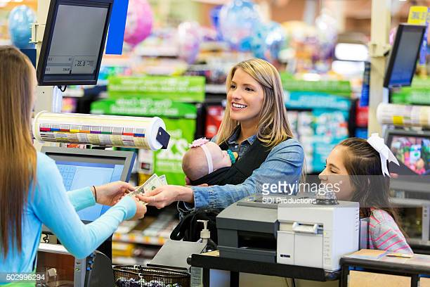 Mother purchasing groceries while shopping with daughters