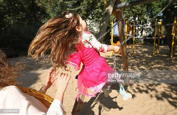 A mother pushes her threeyearold daughter on a swing on September 16 2012 in Berlin Germany Germany is currently debating the introduction of a...
