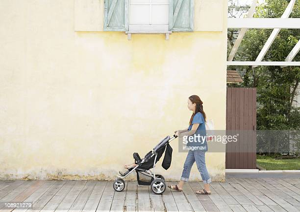 Mother pushing a baby buggy