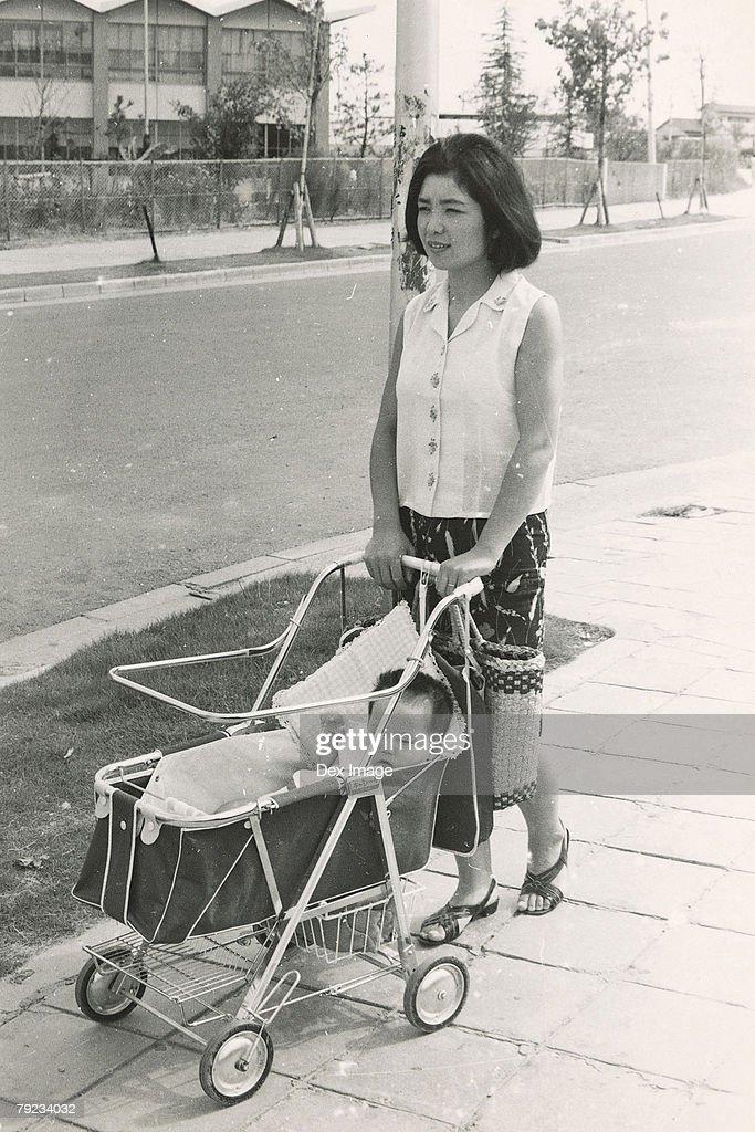 Mother pushing baby pram : Stock Photo