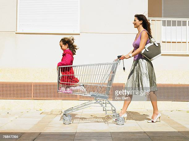 Mother pushing daughter (5-7) in supermarket trolley, Alicante, Spain,