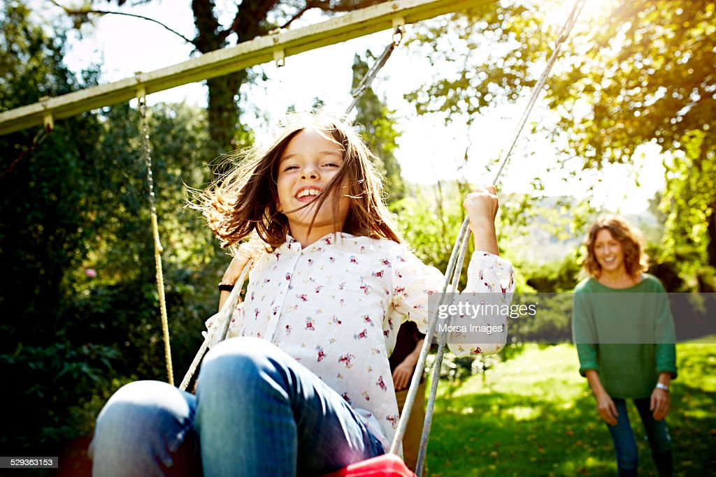 Mother pushing daughter on swing in park