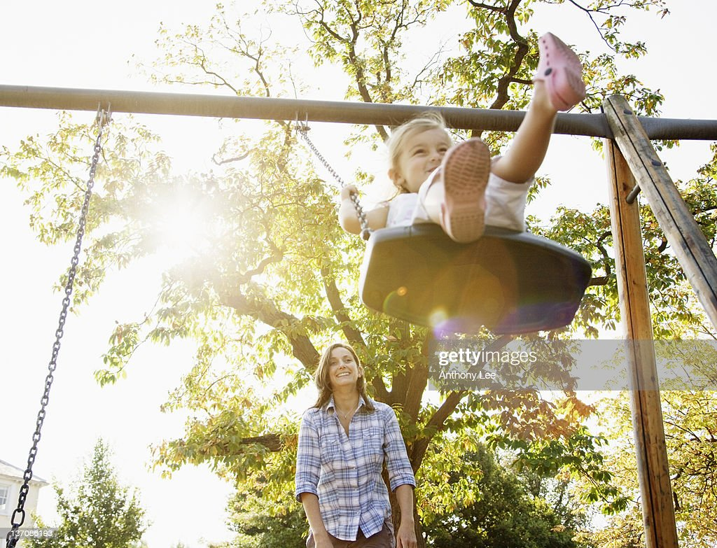 Mother pushing daughter on swing in sunny park : Stock Photo