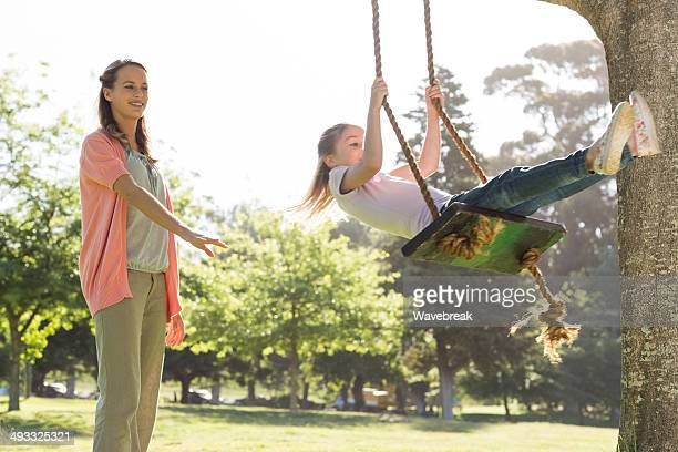 Mother pushing girl on swing