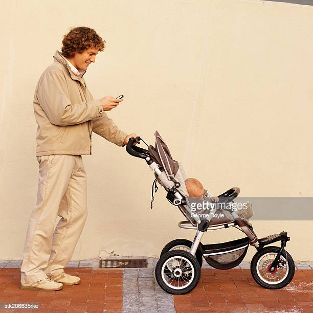 mother pushing her baby (12-18 months) in a buggy while talking on her mobile phone