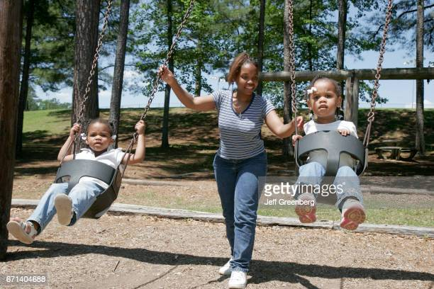 A mother pushing her daughters on the playground swings at Charles Bailey Sportplex