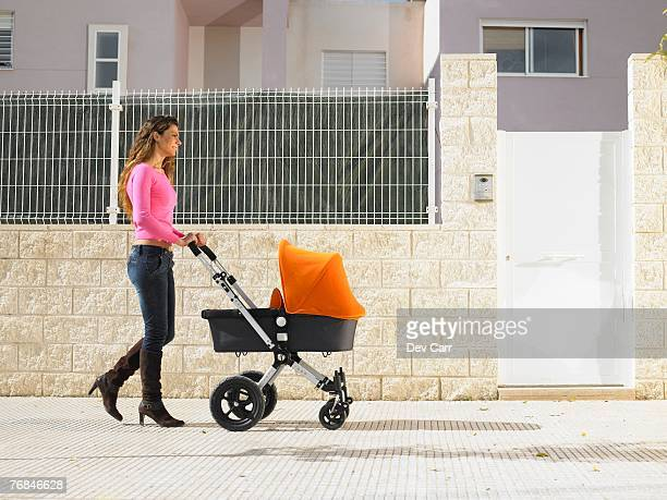 Mother pushing pram on pavement, Alicante, Spain,