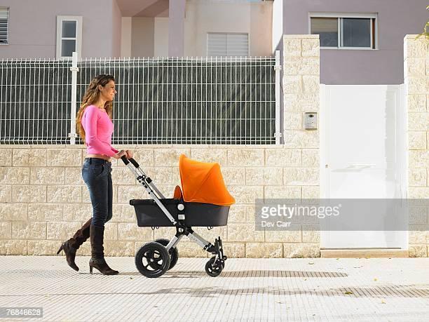 Mother pushing pram on pavement, Alicante, Spain,