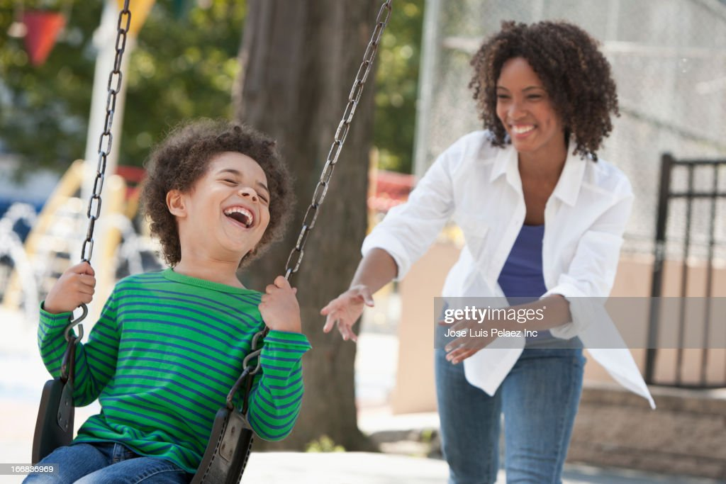 Mother pushing son on swing at park