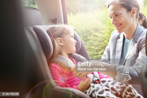 Mother puts daughter in child car seat.