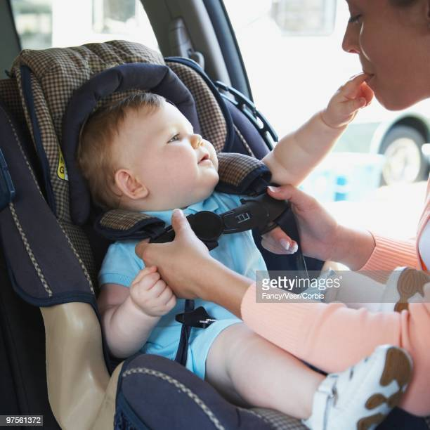 Mother Putting Baby in a Car Seat