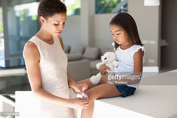 Mother putting bandage on daughter knee