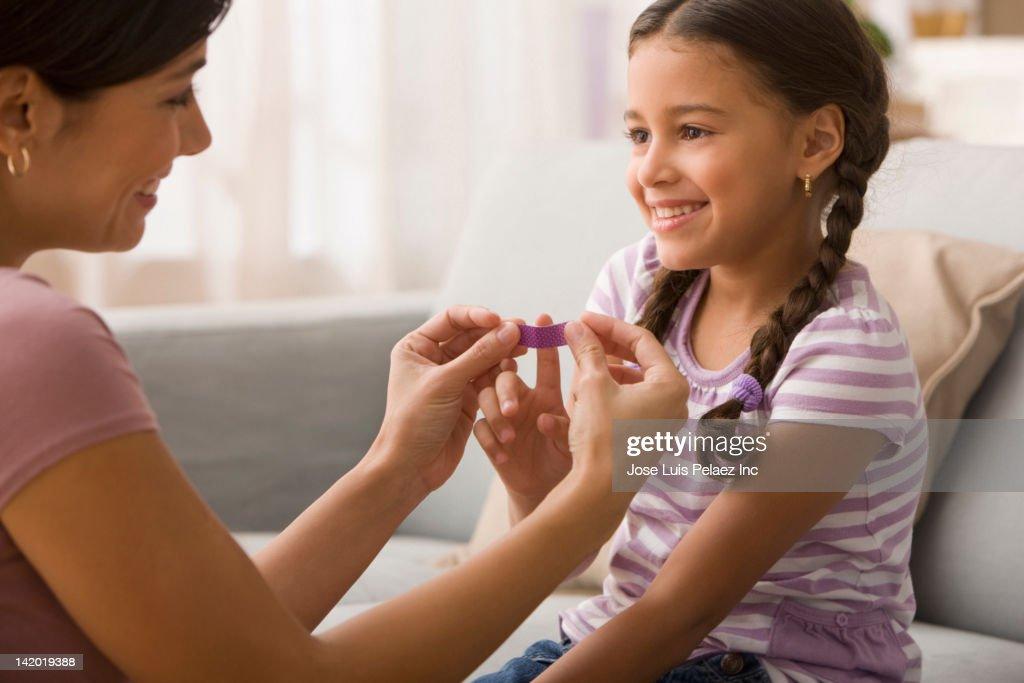Mother putting bandage on daughter's finger