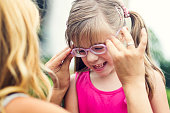 Mother putting eyeglasses on her daughter outdoors