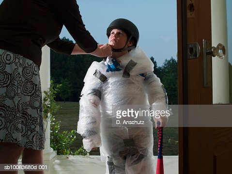 Mother putting helmet on son's (10-11) head wrapped in bubble wrap : Foto stock