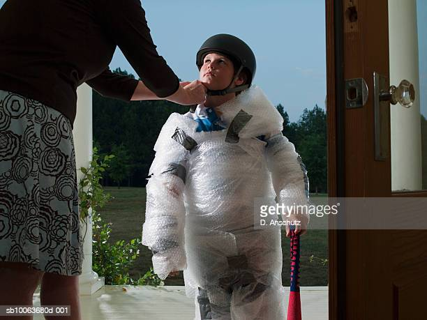Mother putting helmet on son's (10-11) head wrapped in bubble wrap