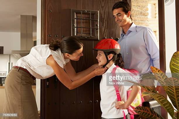 Mother putting helmet to daughter (10-11), father watching