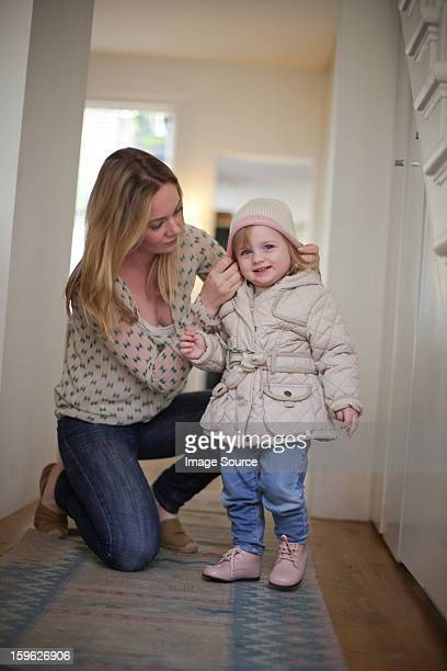 Mother putting knit hat on daughter