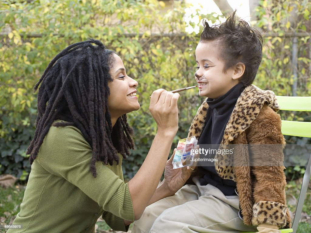 Mother putting makeup on son : Stock Photo