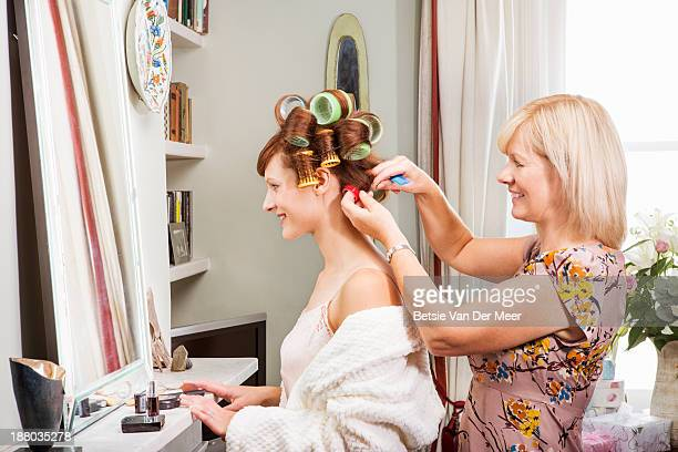 Mother putting rollers in daughters hair.