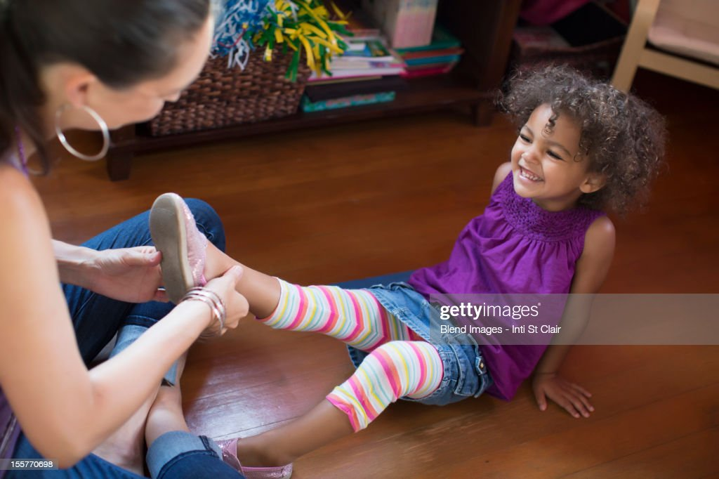Mother putting shoes on daughter : Stock Photo