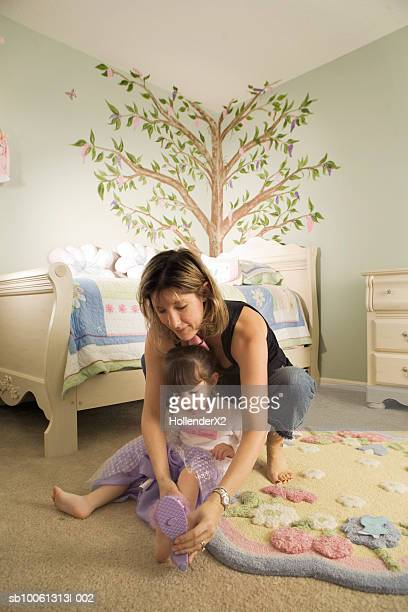 Mother putting shoes on daughter (2-3)