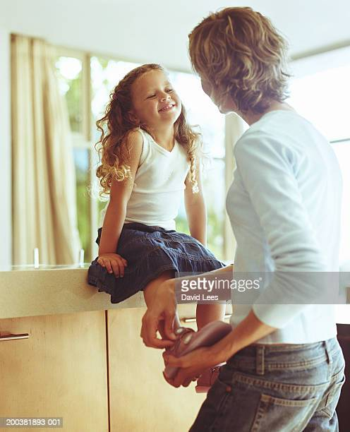 Mother putting shoes on daughter (2-4) sitting on counter, smiling