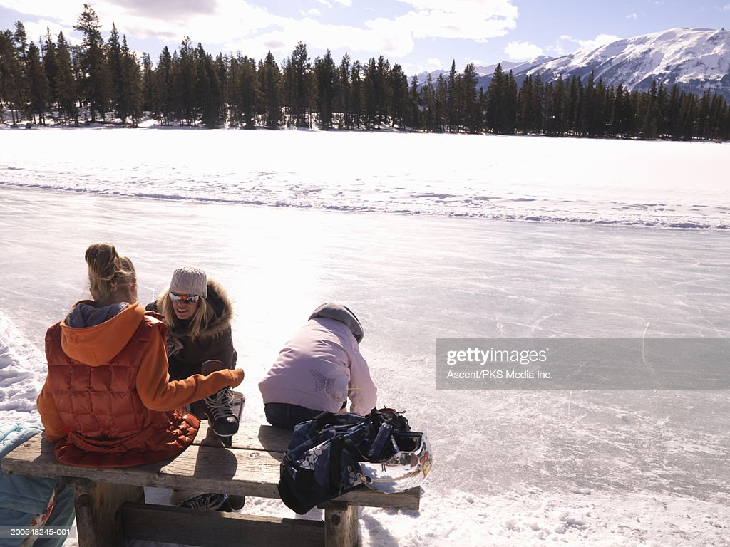 Mother putting skates on girls (10-11) : Stock Photo