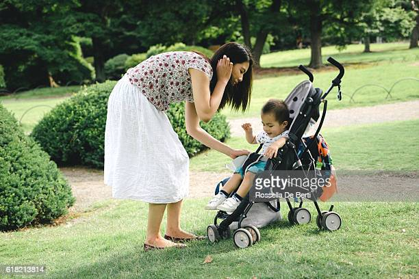 Mother putting son in stroller outdoors, park on the background
