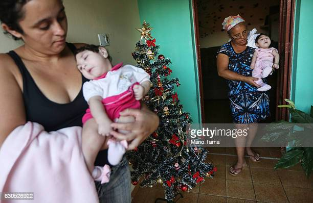Mother Raquel Barbosa carries her daughter Eloisa as grandmother Maria Jose carries twin daughter Eloa both 8 months old and both born with...