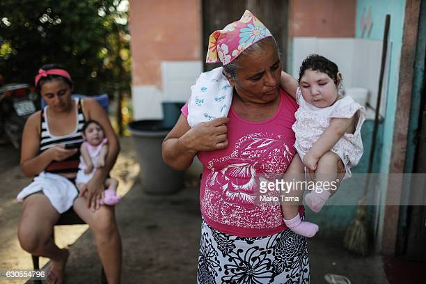 Mother Raquel Barbosa holds her daughter Eloa as grandmother Maria Jose carries twin daughter Eloisa both 8 months old and both born with...