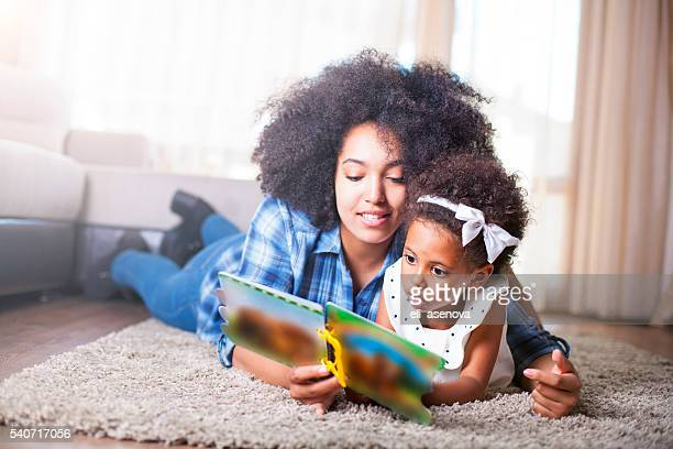 Mother reading a book to her daughter on carpet