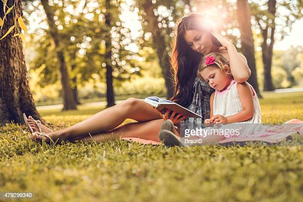 Mother reading a book to her little girl in nature.