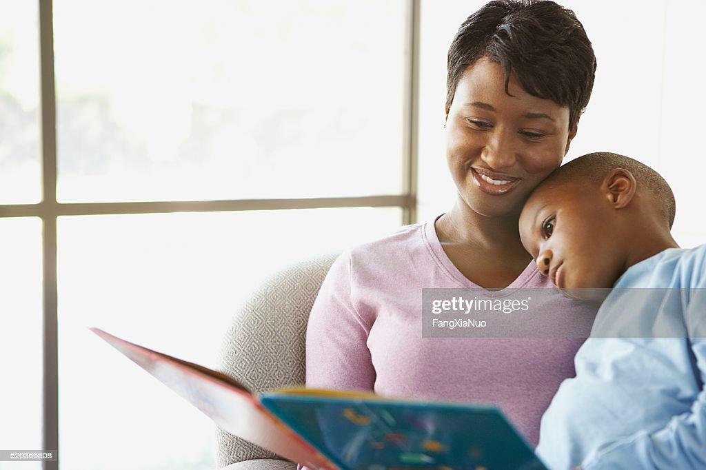 Madre leyendo un cuento a su hijo : Foto de stock