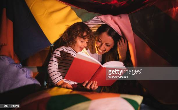 Mother reading a story to her son under bed covers