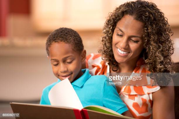 Mother reading at home with young son.